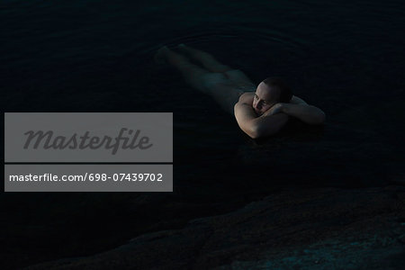 Thoughtful naked man relaxing in water Stock Photo - Premium Royalty-Free, Image code: 698-07439702
