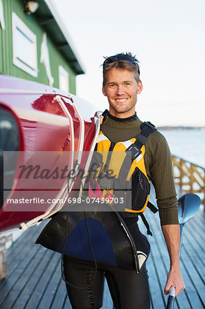 Portrait of confident man carrying kayak on shoulder at boathouse Stock Photo - Premium Royalty-Free, Image code: 698-07439703