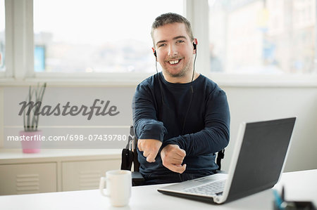 Portrait of happy disabled businessman with laptop at desk in office Stock Photo - Premium Royalty-Free, Image code: 698-07439780