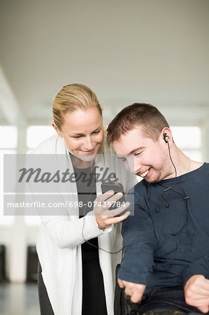 Female caretaker assisting disabled man in using mobile phone at home Stock Photo - Premium Royalty-Free, Image code: 698-07439784