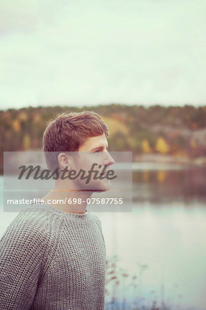 Side view of young man at lakeshore Stock Photo - Premium Royalty-Free, Image code: 698-07587755