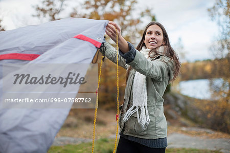 Young woman setting up tent while looking away in forest Stock Photo - Premium Royalty-Free, Image code: 698-07587762