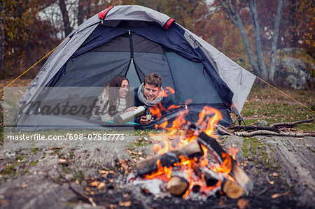 Woman pouring coffee for man while lying in tent at forest Stock Photo - Premium Royalty-Free, Image code: 698-07587773