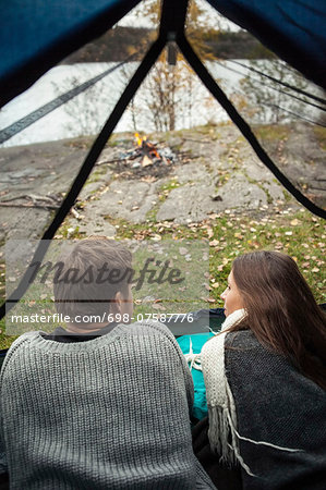 Rear view of young couple lying in tent at lakeshore Stock Photo - Premium Royalty-Free, Image code: 698-07587776