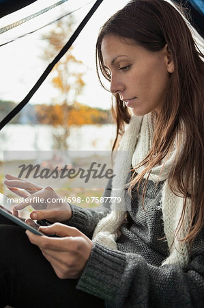Young woman using digital tablet in tent Stock Photo - Premium Royalty-Free, Image code: 698-07587779