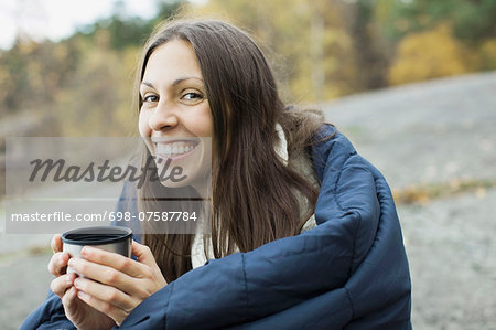 Portrait of happy woman wrapped in blanket holding coffee cup while camping Stock Photo - Premium Royalty-Free, Image code: 698-07587784