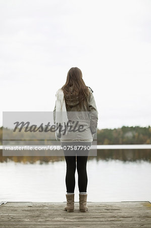 Rear view of woman standing on pier Stock Photo - Premium Royalty-Free, Image code: 698-07587790