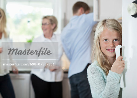 Portrait of smiling girl holding door handle with family in background at kitchen Stock Photo - Premium Royalty-Free, Image code: 698-07587831