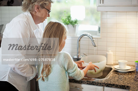 Grandmother and granddaughter washing vegetables in kitchen Stock Photo - Premium Royalty-Free, Image code: 698-07587838