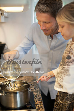Father and daughter cooking in kitchen Stock Photo - Premium Royalty-Free, Image code: 698-07587840