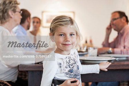 Portrait of girl sitting with family at dining table Stock Photo - Premium Royalty-Free, Image code: 698-07587857