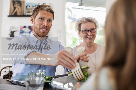 Smiling man serving salad to girl at home Stock Photo - Premium Royalty-Free, Image code: 698-07587860