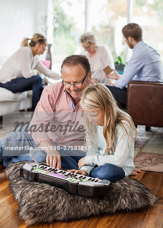 Grandfather and granddaughter playing piano with family in background at home Stock Photo - Premium Royalty-Free, Image code: 698-07587867