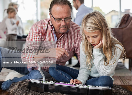 Grandfather and granddaughter playing piano with family in background at home Stock Photo - Premium Royalty-Free, Image code: 698-07587869