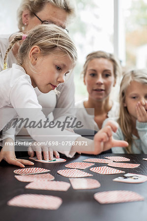 Girl playing card puzzle game with family at home Stock Photo - Premium Royalty-Free, Image code: 698-07587871