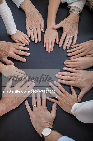 Directly above shot of multi-generation family placing hands in circle Stock Photo - Premium Royalty-Free, Image code: 698-07587875