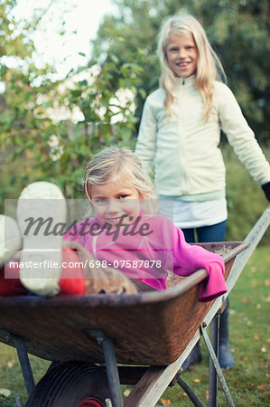 Portrait of playful sisters at yard Stock Photo - Premium Royalty-Free, Image code: 698-07587878