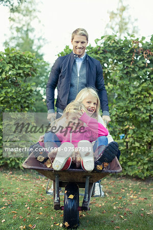 Playful father pushing daughters on wheelbarrow at yard Stock Photo - Premium Royalty-Free, Image code: 698-07587881