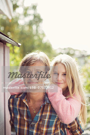 Portrait of smiling mother and daughter at yard Stock Photo - Premium Royalty-Free, Image code: 698-07587912
