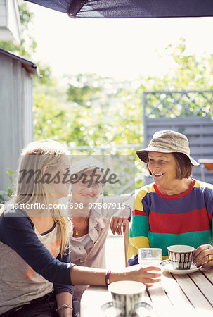 Three generation females having coffee in yard Stock Photo - Premium Royalty-Free, Image code: 698-07587916