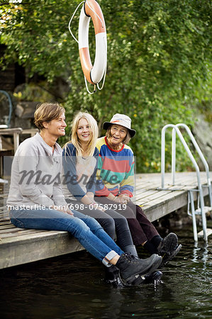 Three generation females sitting on pier Stock Photo - Premium Royalty-Free, Image code: 698-07587919