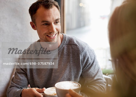 Young man having coffee with woman at cafe Stock Photo - Premium Royalty-Free, Image code: 698-07587934