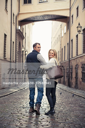 Full length of happy couple walking on city street Stock Photo - Premium Royalty-Free, Image code: 698-07587941