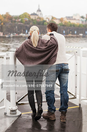 Rear view of young couple leaning on railing outdoors Stock Photo - Premium Royalty-Free, Image code: 698-07587949