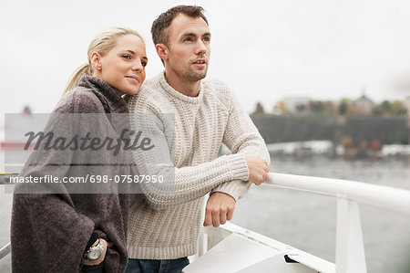 Young couple leaning on railing outdoors Stock Photo - Premium Royalty-Free, Image code: 698-07587950