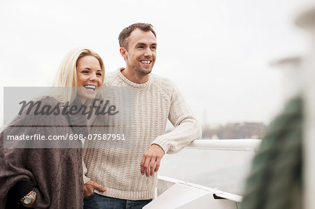 Happy young couple leaning on railing outdoors Stock Photo - Premium Royalty-Free, Image code: 698-07587951
