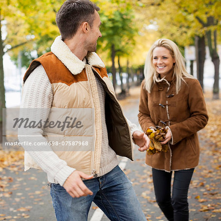 Playful young couple on street during autumn Stock Photo - Premium Royalty-Free, Image code: 698-07587968