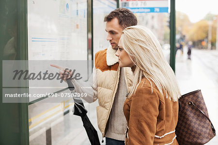 Young couple reading time table on bus stop Stock Photo - Premium Royalty-Free, Image code: 698-07587969