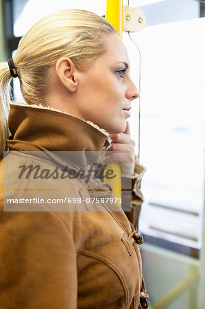 Side view of woman holding railing on bus Stock Photo - Premium Royalty-Free, Image code: 698-07587971
