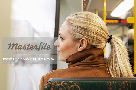 Rear view of woman looking out through bus window Stock Photo - Premium Royalty-Free, Image code: 698-07587974