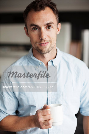 Portrait of confident businessman holding coffee mug in office Stock Photo - Premium Royalty-Free, Image code: 698-07587977