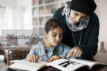 Mother assisting girl in doing homework at table Stock Photo - Premium Royalty-Free, Image code: 698-07588000