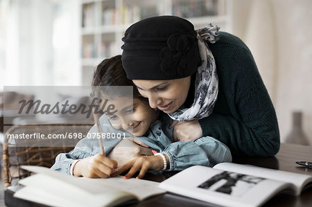 Mother embracing daughter studying at home Stock Photo - Premium Royalty-Free, Image code: 698-07588001