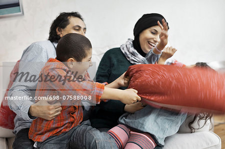 Playful Muslim family in living room Stock Photo - Premium Royalty-Free, Image code: 698-07588008