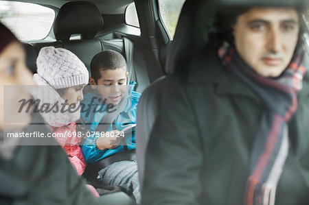 Siblings using digital tablet while on road trip with parents Stock Photo - Premium Royalty-Free, Image code: 698-07588024