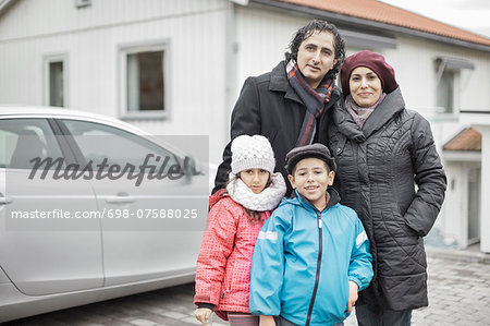 Portrait of happy Muslim family in warm clothing standing outside house Stock Photo - Premium Royalty-Free, Image code: 698-07588025