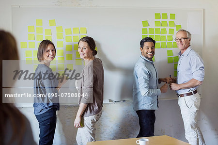 Happy business people standing by whiteboard at office Stock Photo - Premium Royalty-Free, Image code: 698-07588044