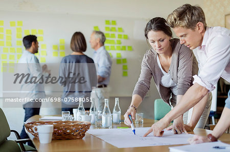 Business people discussing over blueprint at conference table Stock Photo - Premium Royalty-Free, Image code: 698-07588051