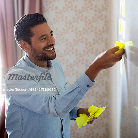 Smiling businessman removing memo notes from whiteboard in office Stock Photo - Premium Royalty-Free, Image code: 698-07588052