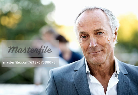 Portrait of confident senior businessman at patio with colleagues in background Stock Photo - Premium Royalty-Free, Image code: 698-07588075