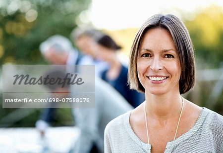 Portrait of happy businesswoman at patio with colleagues in background Stock Photo - Premium Royalty-Free, Image code: 698-07588076