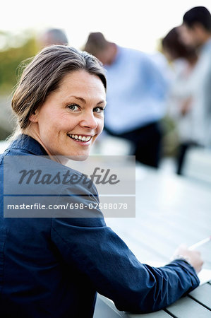 Portrait of happy businesswoman at patio with colleagues in background Stock Photo - Premium Royalty-Free, Image code: 698-07588078