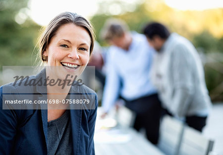 Portrait of businesswoman laughing at patio with colleagues in background Stock Photo - Premium Royalty-Free, Image code: 698-07588079