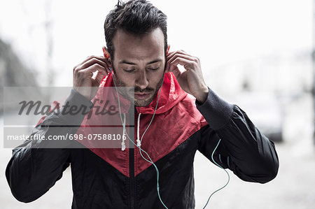 Sporty man in jacket adjusting headphones Stock Photo - Premium Royalty-Free, Image code: 698-07588106