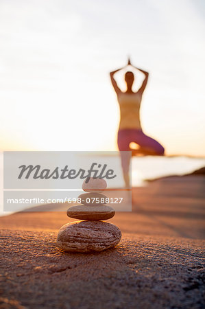 Pile of stones with woman practicing yoga in background at lakeshore Stock Photo - Premium Royalty-Free, Image code: 698-07588127
