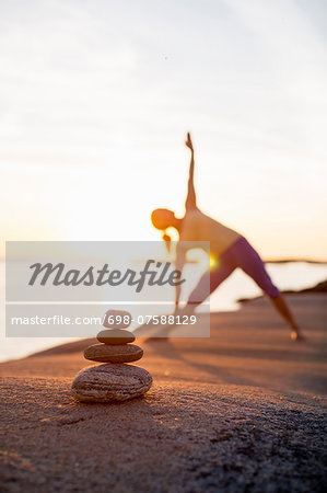 Woman practices yoga on lakeshore with focus on stack of stones Stock Photo - Premium Royalty-Free, Image code: 698-07588129